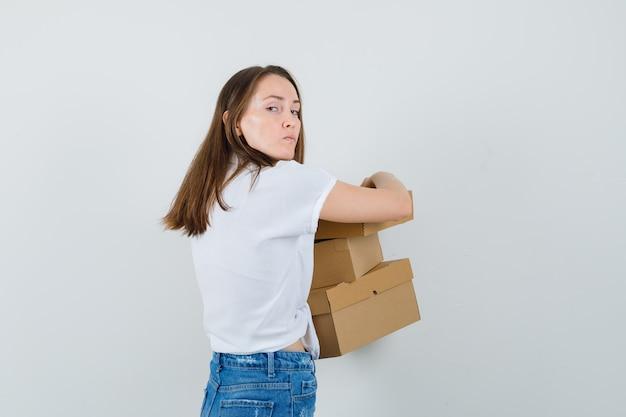 Mooie dame in witte blouse die dozen vasthoudt terwijl ze ze niet wil delen.