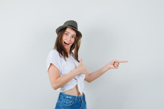 Mooie dame in witte blouse, hoed opzij wijzend terwijl duim omhoog wordt getoond en vrolijk, vooraanzicht kijkt.