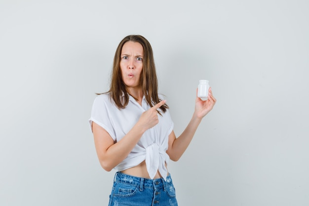 Mooie dame in witte blouse, spijkerbroek fles pillen kijken en op zoek verward, vooraanzicht.