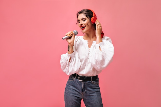 Mooie dame in witte blouse zingt en luistert naar muziek in de koptelefoon. mooie jonge vrouw in stijlvolle outfit poseren op roze achtergrond.