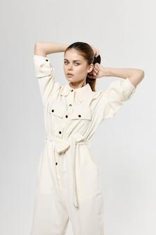 Mooie dame in witte jumpsuit raakt haar op haar hoofd met haar handen en mode licht.