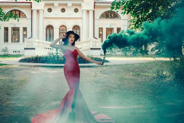 Mooie dame is poseren in een sexy rode jurk