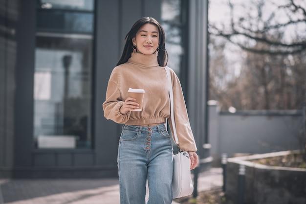 Mooie dame. langharige jonge aziatische vrouw die in de straat loopt