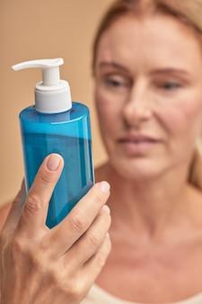 Mooie dame leest etiket op cosmetische fles in studio