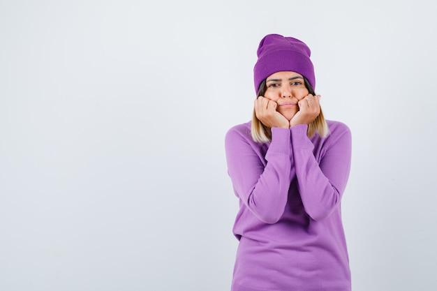 Mooie dame leunt wangen op handen in trui, muts en ziet er schattig uit, vooraanzicht.