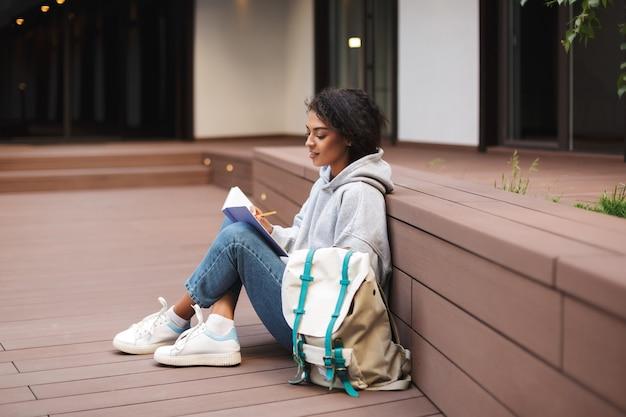 Mooie dame met donker krullend haar, zittend op de vloer en schrijven in notitieblok terwijl ze alleen studeert op de binnenplaats van de universiteit