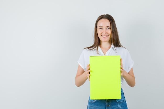 Mooie dame met doos terwijl lachend in witte blouse, spijkerbroek en op zoek blij, vooraanzicht. ruimte voor tekst