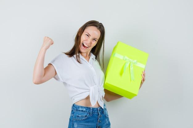 Mooie dame met doos terwijl winnaar gebaar in witte blouse, spijkerbroek en vrolijk, vooraanzicht wordt weergegeven.