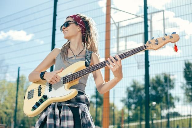 Mooie dame met dreadlocks zonnebril dragen en glimlachen terwijl ze in de verte kijken en gitaar spelen op het sportveld