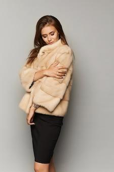 Mooie dame met elegant kapsel in luxe bontjas, geïsoleerd op de achtergrond. mode kunstbont. mooie vrouw in luxe bontjas.