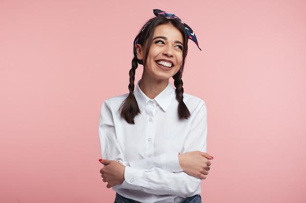 Mooie dame met gekruiste armen lachend over roze