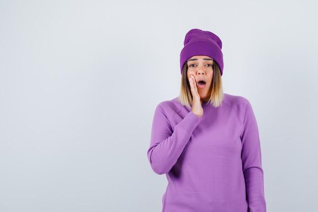 Mooie dame met hand in de buurt van mond in trui, muts en geschokt kijken. vooraanzicht.