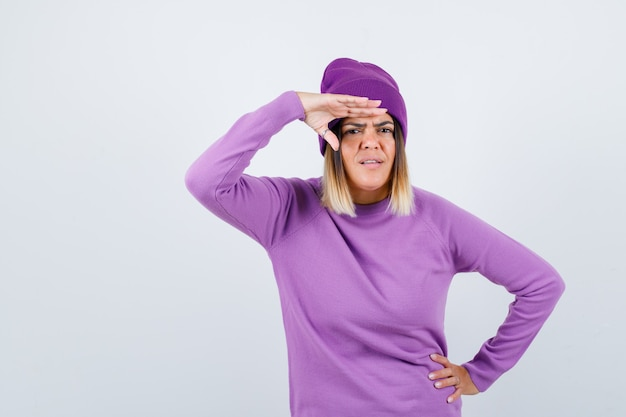 Mooie dame met hand over hoofd in trui, muts en verward, vooraanzicht.