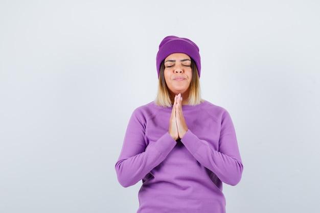 Mooie dame met handen in biddend gebaar in trui, muts en hoopvol kijkend, vooraanzicht.