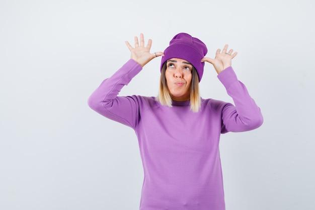Mooie dame met handen in de buurt van hoofd als oren in trui, muts en er grappig uitzien, vooraanzicht.