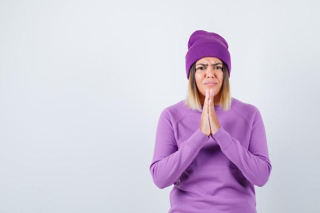 Mooie dame met handen in gebedsgebaar in trui, muts en ongezellig kijken. vooraanzicht.