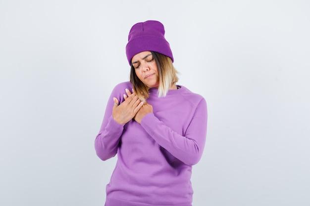 Mooie dame met handen op de borst in trui, muts en boos, vooraanzicht.