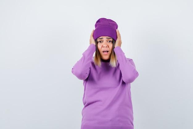 Mooie dame met handen op het hoofd in trui, muts en met afschuw vervuld. vooraanzicht.