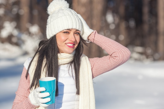 Mooie dame met koffiekop in wintertijd in openlucht