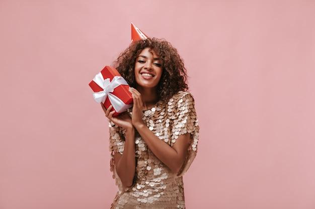 Mooie dame met krullend haar in beige jurk en vakantiepet glimlachend en met rode geschenkdoos op geïsoleerde roze muur..