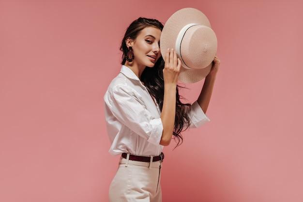 Mooie dame met lang golvend haar in moderne bruine oorbellen, lichte blouse en coole broek bedekt haar oog met hoed op roze muur