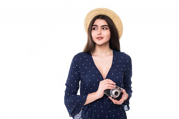 Mooie dame model in korte blauwe jurk en hoed met retrocamera in haar handen op wit