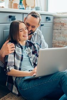 Mooie dame op de keukenvloer, zittend met een laptop en haar liefhebbende vriend die haar schouder knuffelt