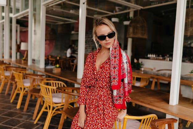 Mooie dame poseren op terras, heldere zomerjurk, zonnebril en accessoires dragen