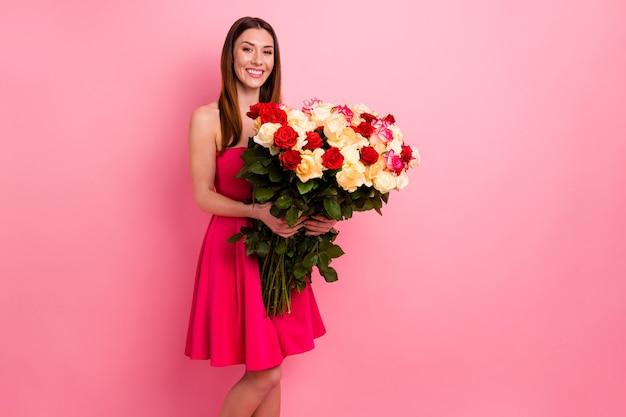 Mooie dame poseren tegen de roze muur met een boeket kleurrijke rozen