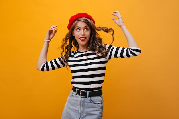 Mooie dame speelt haar krullend haar op een oranje achtergrond. fanny jonge vrouw in rode baret, gestreepte blouse en denim rok poseren op geïsoleerde achtergrond.