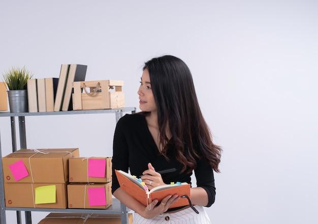 Mooie dame staand naast brievenbusplank, bestelling controleren en op boek schrijven, voorbereiden op verpakking, werkende e-commerce, zakenvrouw