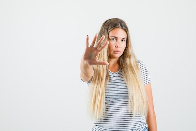 Mooie dame stop gebaar in t-shirt tonen en serieus kijken. vooraanzicht.