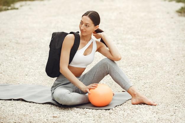 Mooie dame training op een zomerstrand. brunette doet yoga. meisje in een sportpak.