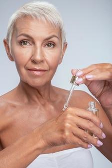 Mooie dame van middelbare leeftijd die in de camera kijkt en serum op de rug van haar hand doet