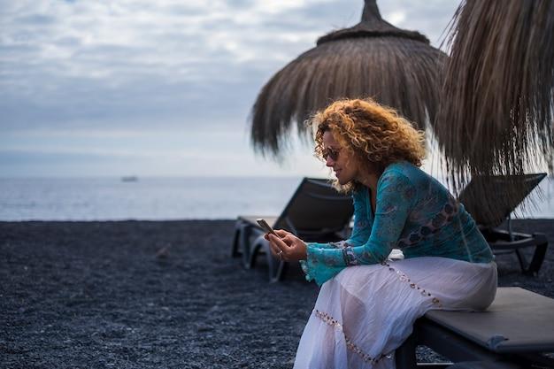 Mooie dame van middelbare leeftijd met behulp van technologie slimme telefoon op het strand tijdens winterseizoen vakantie alleen. casual hippie chique jurk en glimlach. oceaan. blauwe tinten. onafhankelijkheid concept Premium Foto