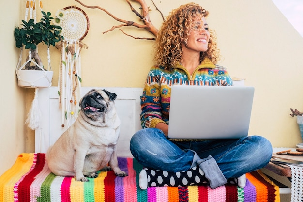 Mooie dame van middelbare leeftijd met krullend haar werkt met een laptop buiten thuis op het terras glimlachend en kijkend naar zijn zijde