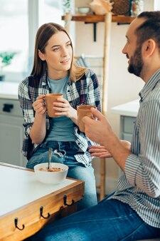 Mooie dame zit met een man in de keuken en drinkt thee Premium Foto