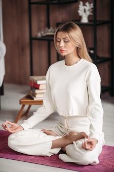 Mooie dame zittend op de lotuspositie op de vloer met gesloten ogen. gezond en levensstijlconcept
