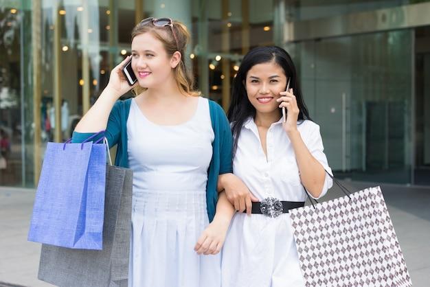 Mooie dames die op smartphones en winkelen praten