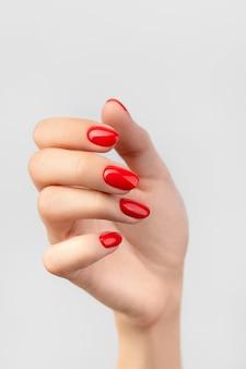 Mooie dames hand met rode manicure op grijs
