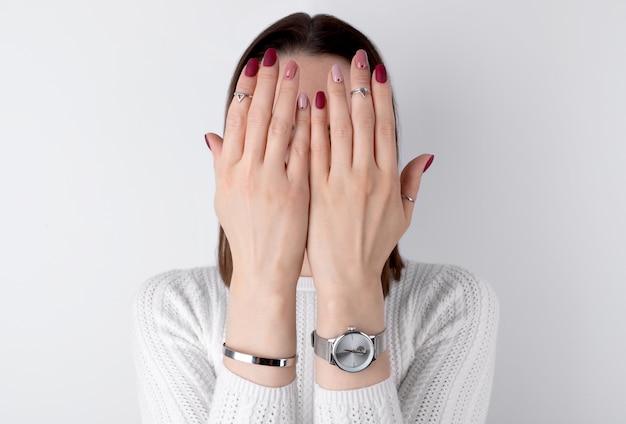 Mooie dames handen met een roze manicure in minimalistische stijl
