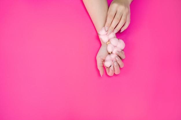 Mooie dames manicure in delicate tinten, op een lichte achtergrond met zacht roze katoen.