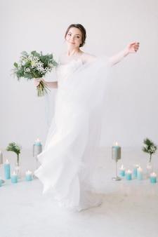 Mooie dansende bruid voor bruiloft decoraties met bloemen en kaarsen