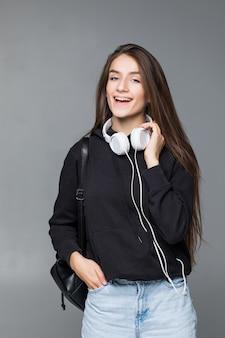Mooie dansende vrouwelijke vrouw in koptelefoon terwijl u luistert naar de muziek over witte muur