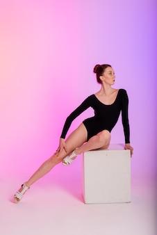 Mooie danseres die zwarte en hoge hakken draagt tijdens het uitvoeren van paaldans trucs, neon