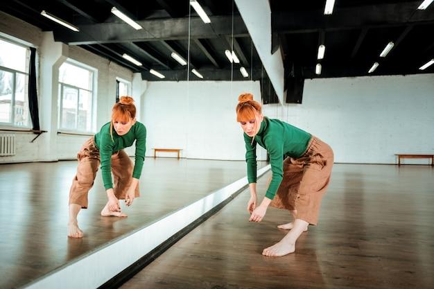Mooie danseres. vrij roodharige professionele danseres draagt een oranje broek en kijkt geconcentreerd tijdens het dansen in de buurt van de spiegel