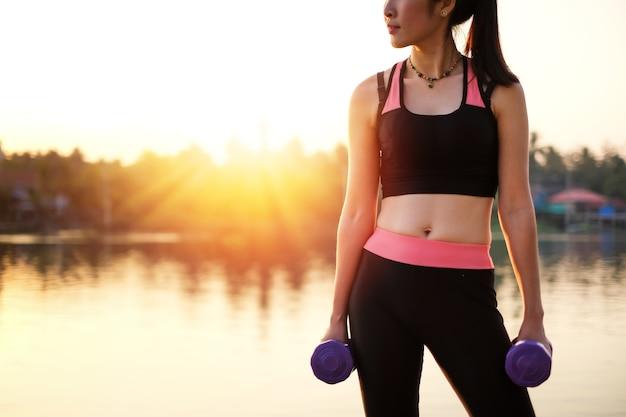Mooie de vrouwenoefening van azië door gewicht in sexy sportslijtage dichtbij de rivier op te heffen