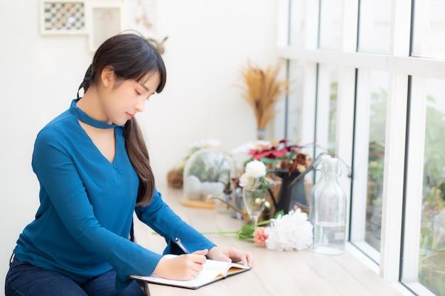 Mooie de vrouwenschrijver die van portret jonge azië op notitieboekje of agenda met gelukkig schrijven