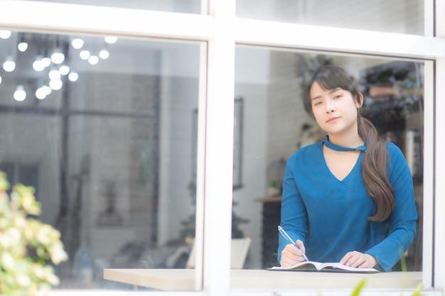 Mooie de vrouwenschrijver die van portret jonge azië op notitieboekje schrijven