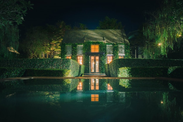 Mooie decoratie van engelse landelijke stijl gebouw bedekt met groene klimplant 's nachts